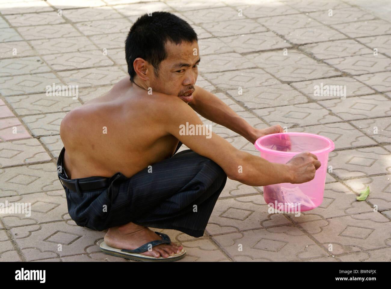 Deformed man begging on street, Yunnan, China - Stock Image