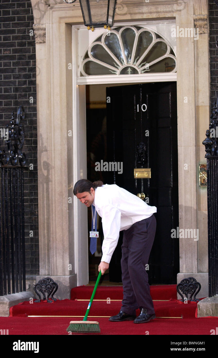 Last minute sweeping for the red carpet at number 10 Downing Street ready for arrivals for dinner of former Prime - Stock Image