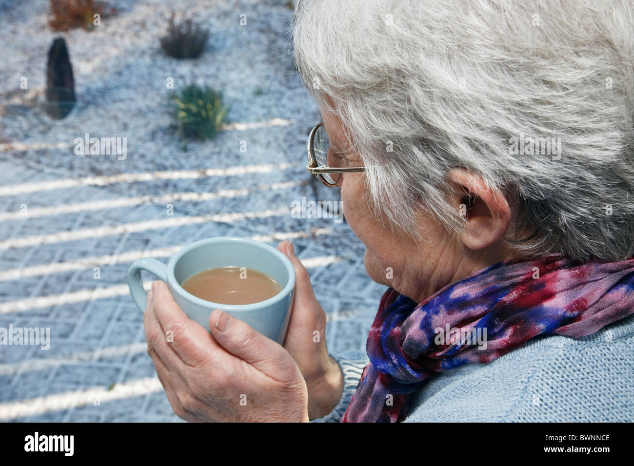 Everyday hygge scene with senior woman living alone wearing a scarf and holding a warm drink looking out of a window - Stock Image