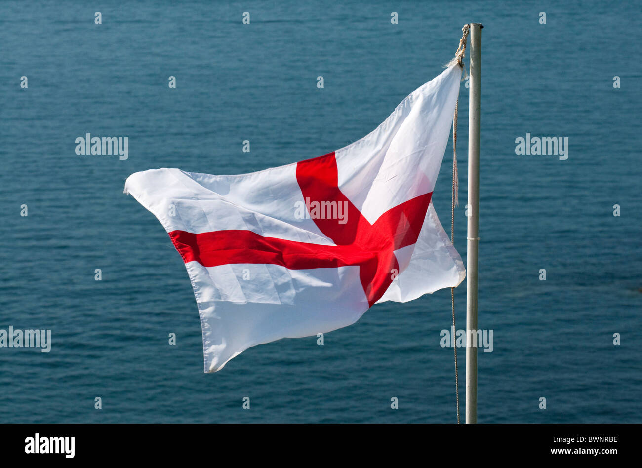 Cross of Saint George flag, national flag of England, with sea beyond - Stock Image