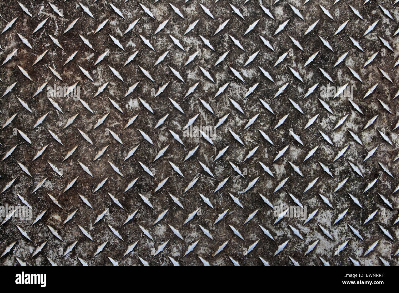 dirty worn old aluminum diamond plate non-skid surface background - Stock Image
