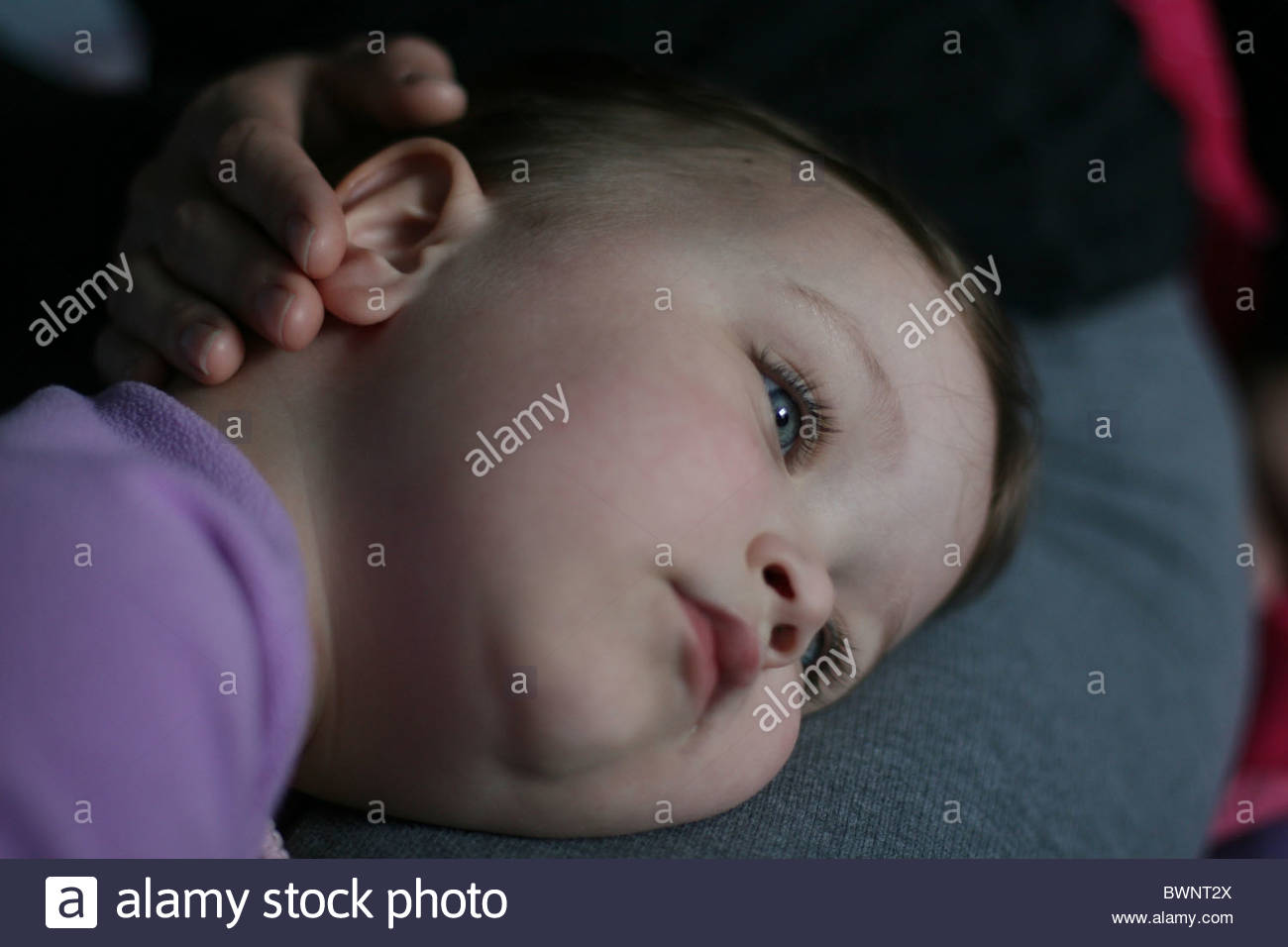 A two year old girl with her head on her mother's lap. - Stock Image