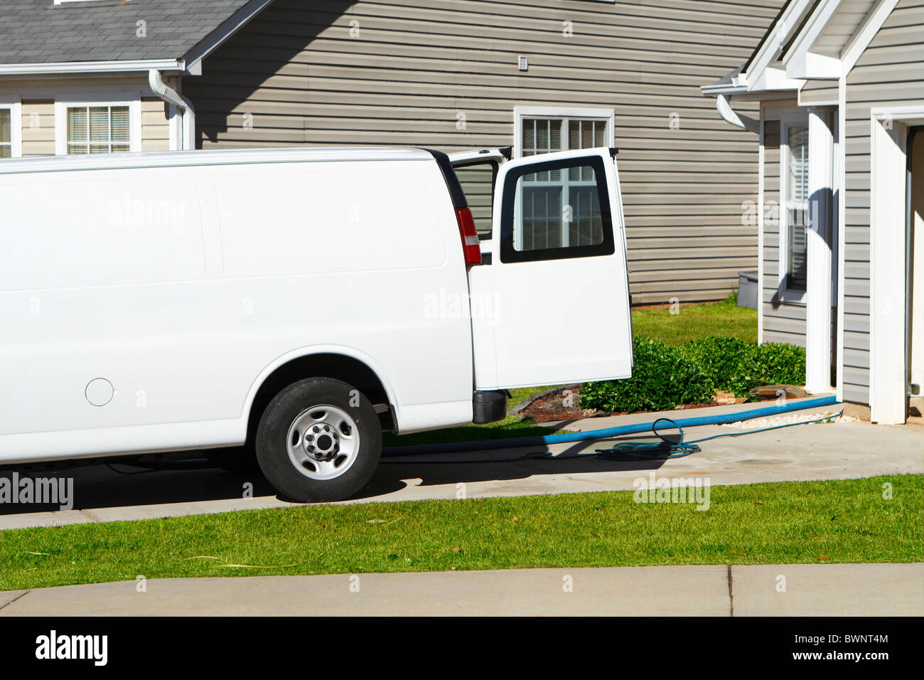 Professional carpet & upholstery cleaning service van with hoses coming out the back of the vehicle in an American Stock Photo