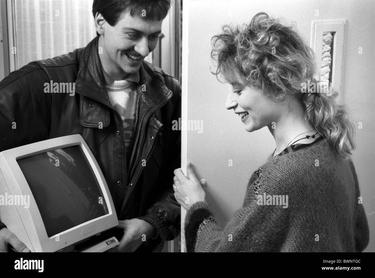 1981 Woman getting her first computer from man standing at front door holding computer screen in his hands, both - Stock Image