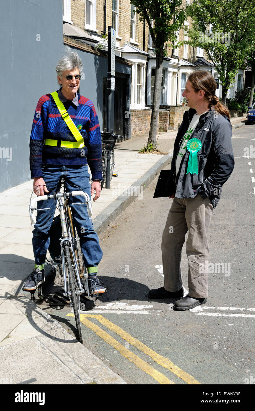 Two male Green Party activists, one on a bike, talking in the street whilst out electioneering, one is wearing a - Stock Image