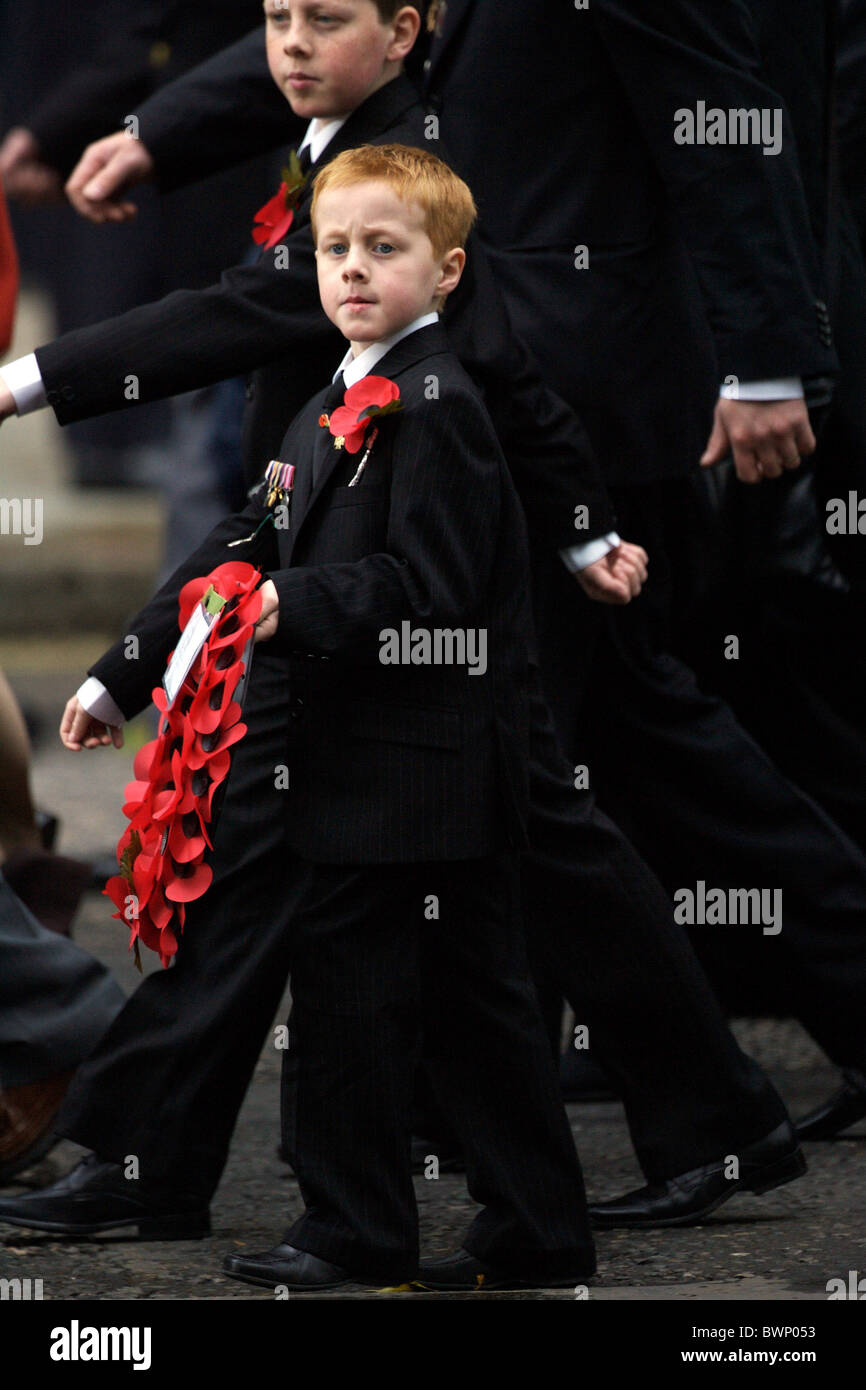 Boy with wreath of red poppies at the Cenotaph in Whitehall on Remembrance Sunday to commemorate the war dead - Stock Image