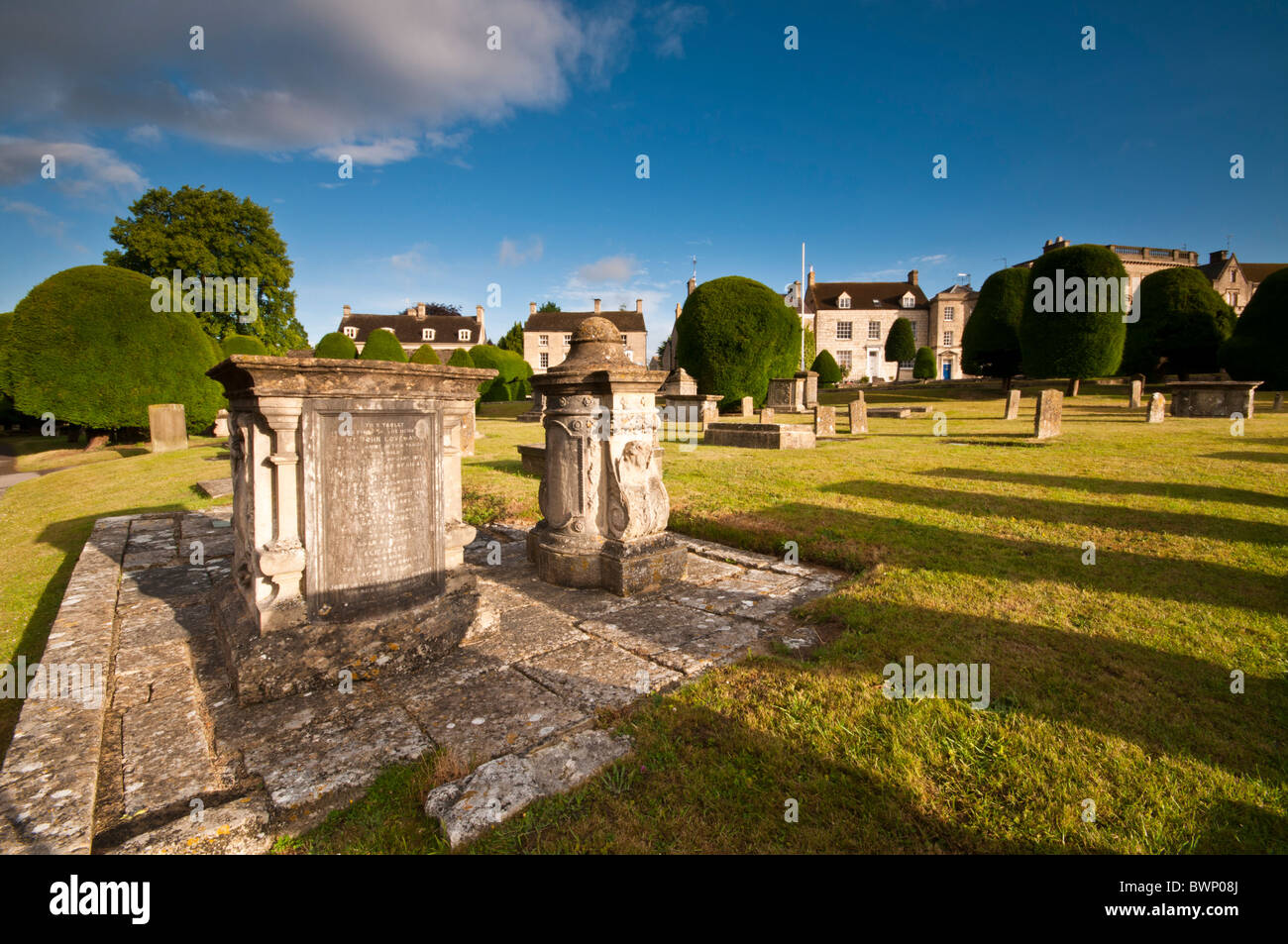 St Mary's Churchyard with yew trees and Cotswold stone cottages in the background, Painswick, Gloucestershire, - Stock Image