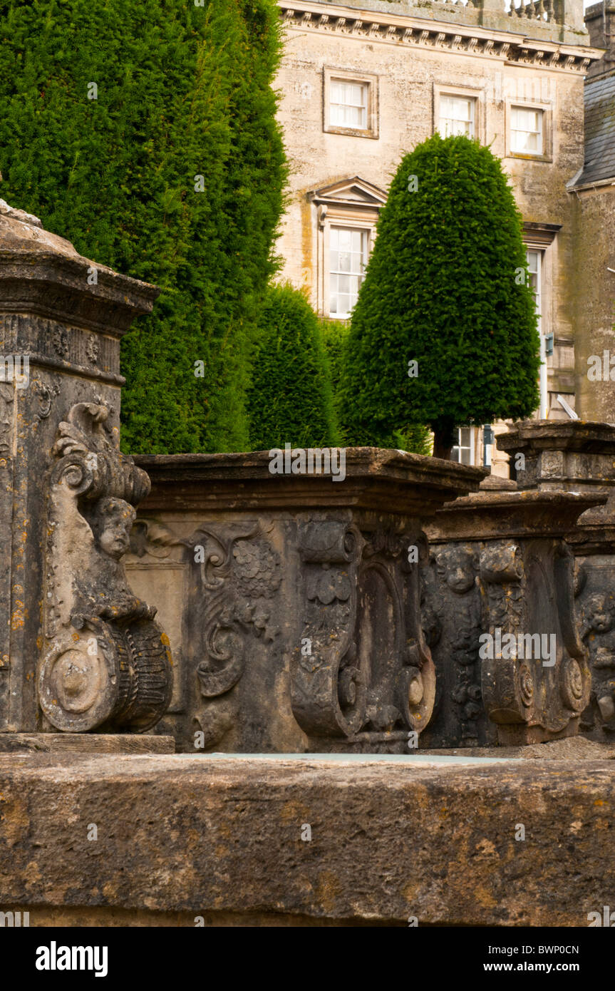 St Mary's Churchyard with yew trees and Cotswold stone building in the background, Painswick, Gloucestershire, - Stock Image