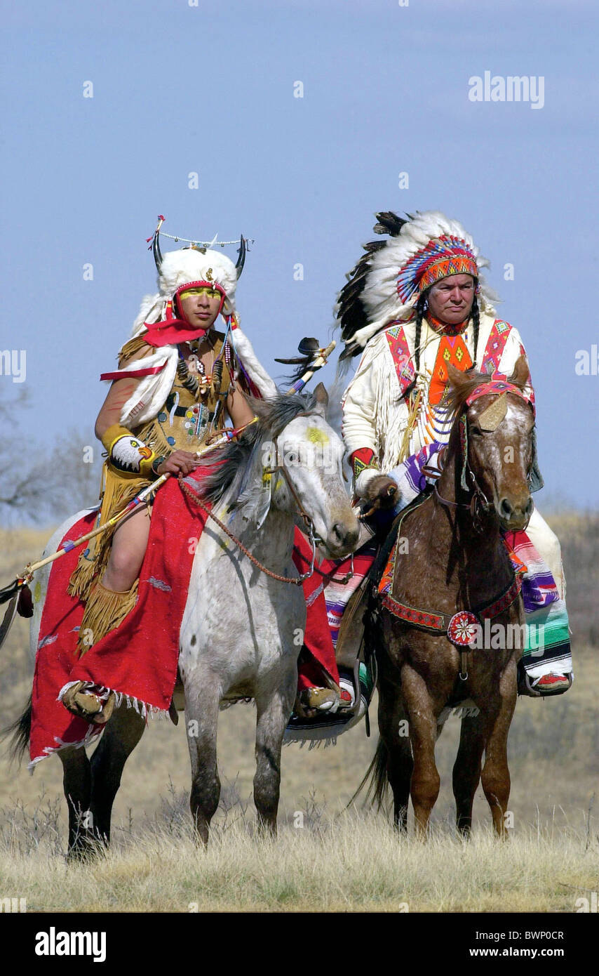 CANADIAN PLAINS INDIANS ON HORSEBACK IN TRADITIONAL COSTUMES AND FEATHER HEAD DRESS WANUSKEWIN HERITAGE PARK SASKATOON - Stock Image