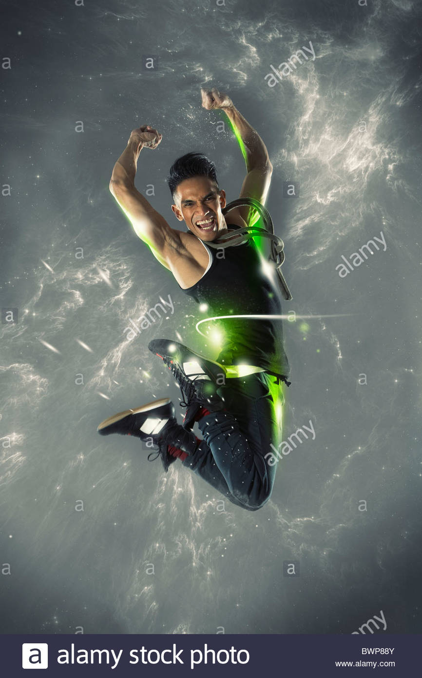 Excited man jumping in mid-air - Stock Image