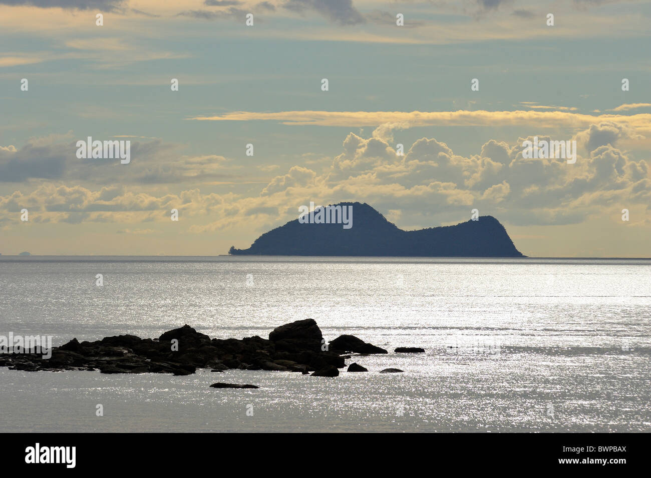 Satang Island in silhouette on the South China Sea, Sarawak, Malaysia, Asia. View from Damai beach. - Stock Image
