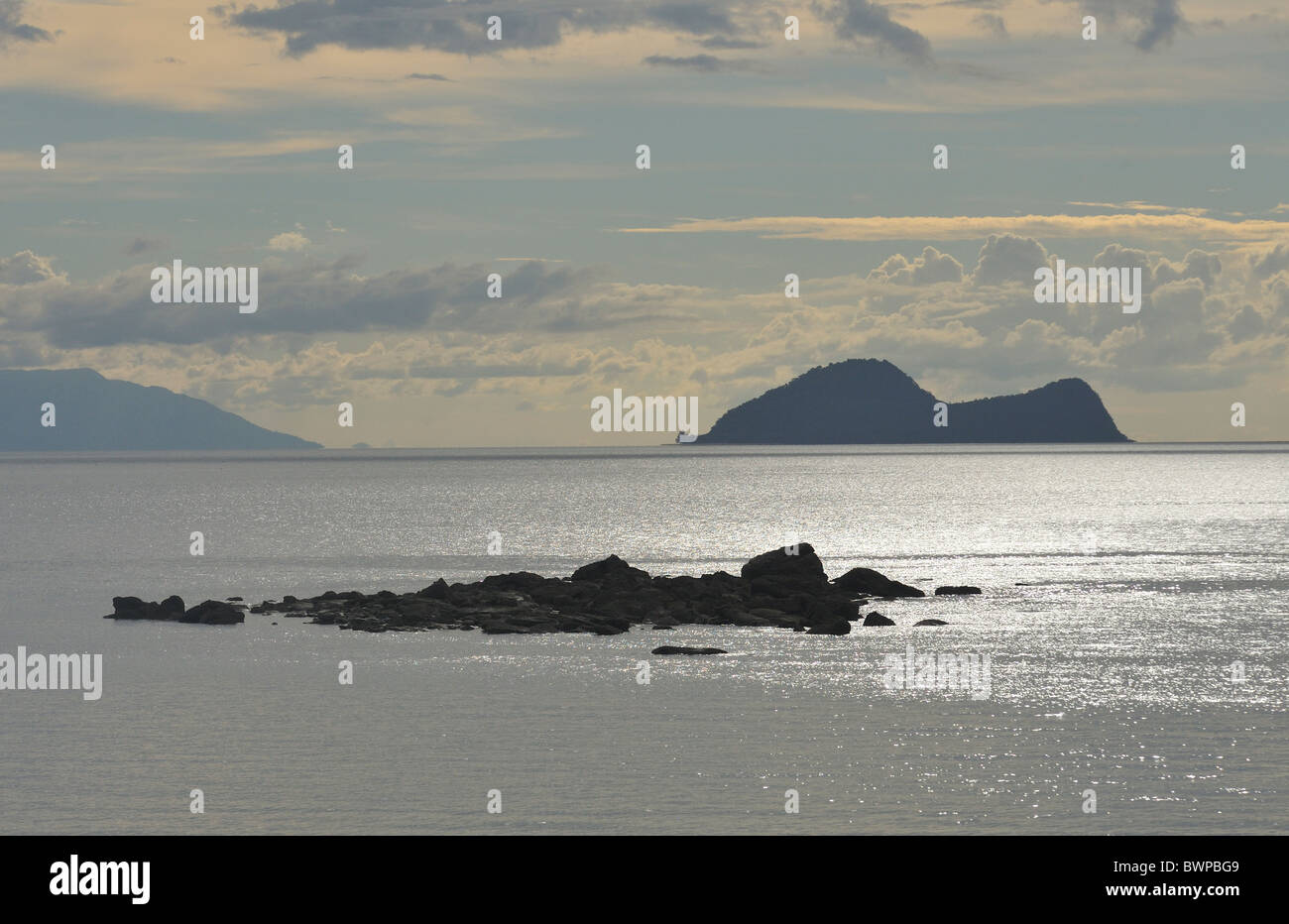 Satang Island in silhouette on the South China Sea, Sarawak, Malaysia, Asia - Stock Image