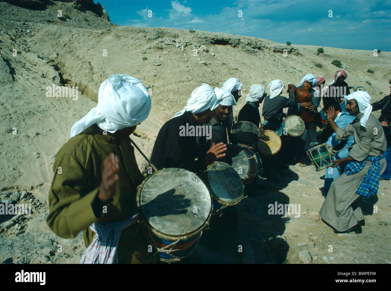BAHRAIN Middle East Gulf State Music Musicians playing drums in a desert landscape Stock Photo