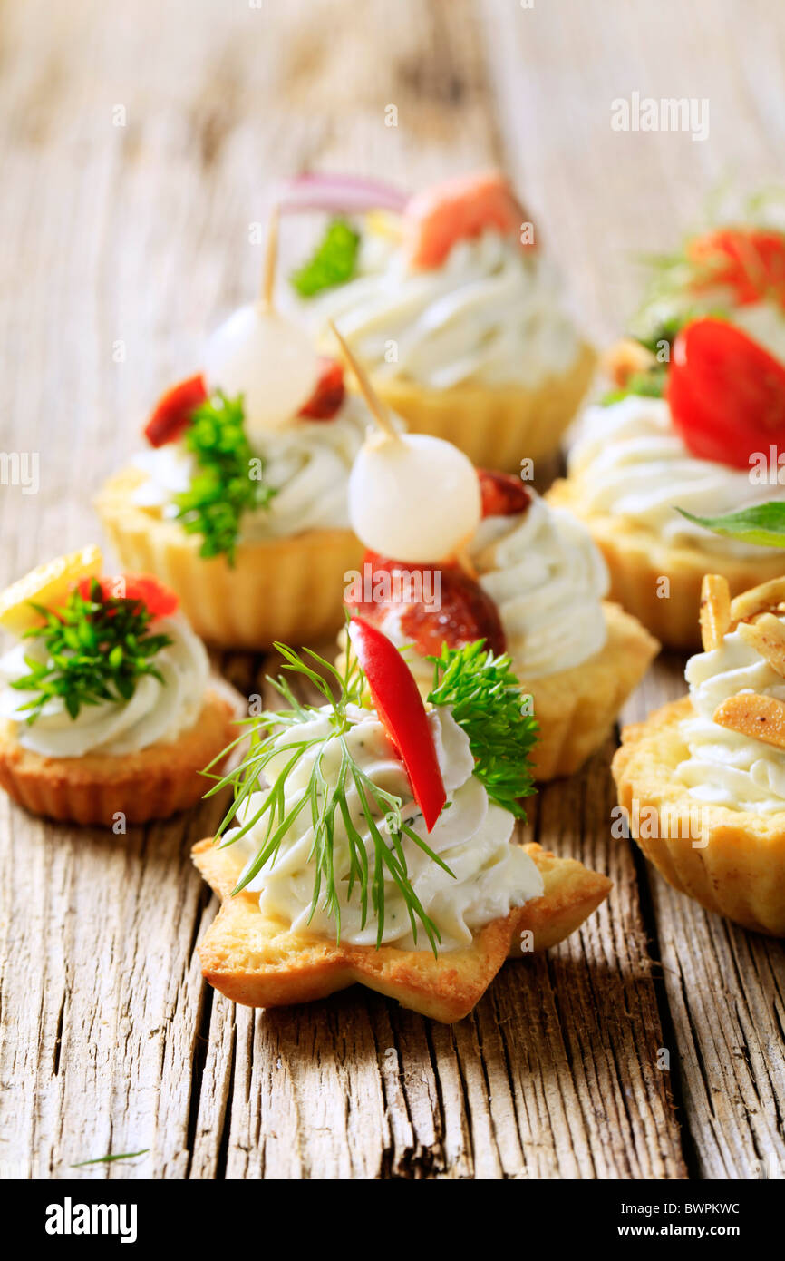 Variety of pastry-based canapes with various toppings - Stock Image
