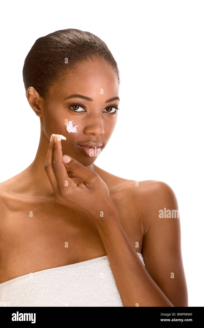 Beautiful young ethnic woman with Slicked Back Hair wrapped in white bath towel applying moisturizer on her face - Stock Image