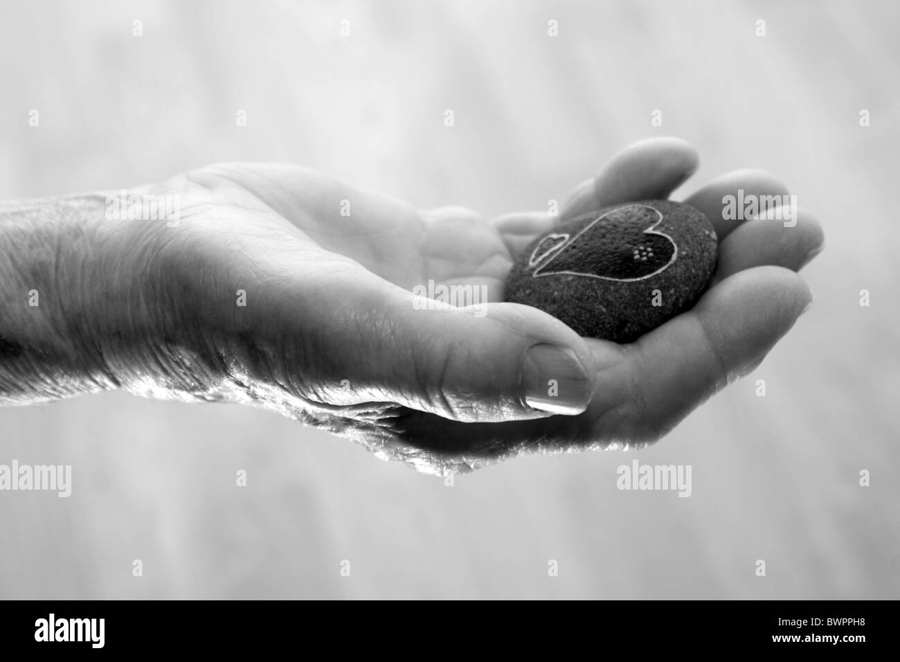 hand of old woman and the heart on the stone - Stock Image