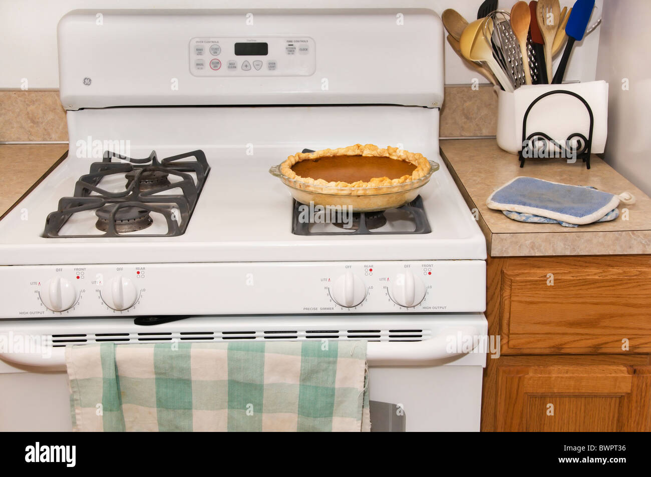 A freshly baked homemade pumpkin pie cools on top of the stove in a ...