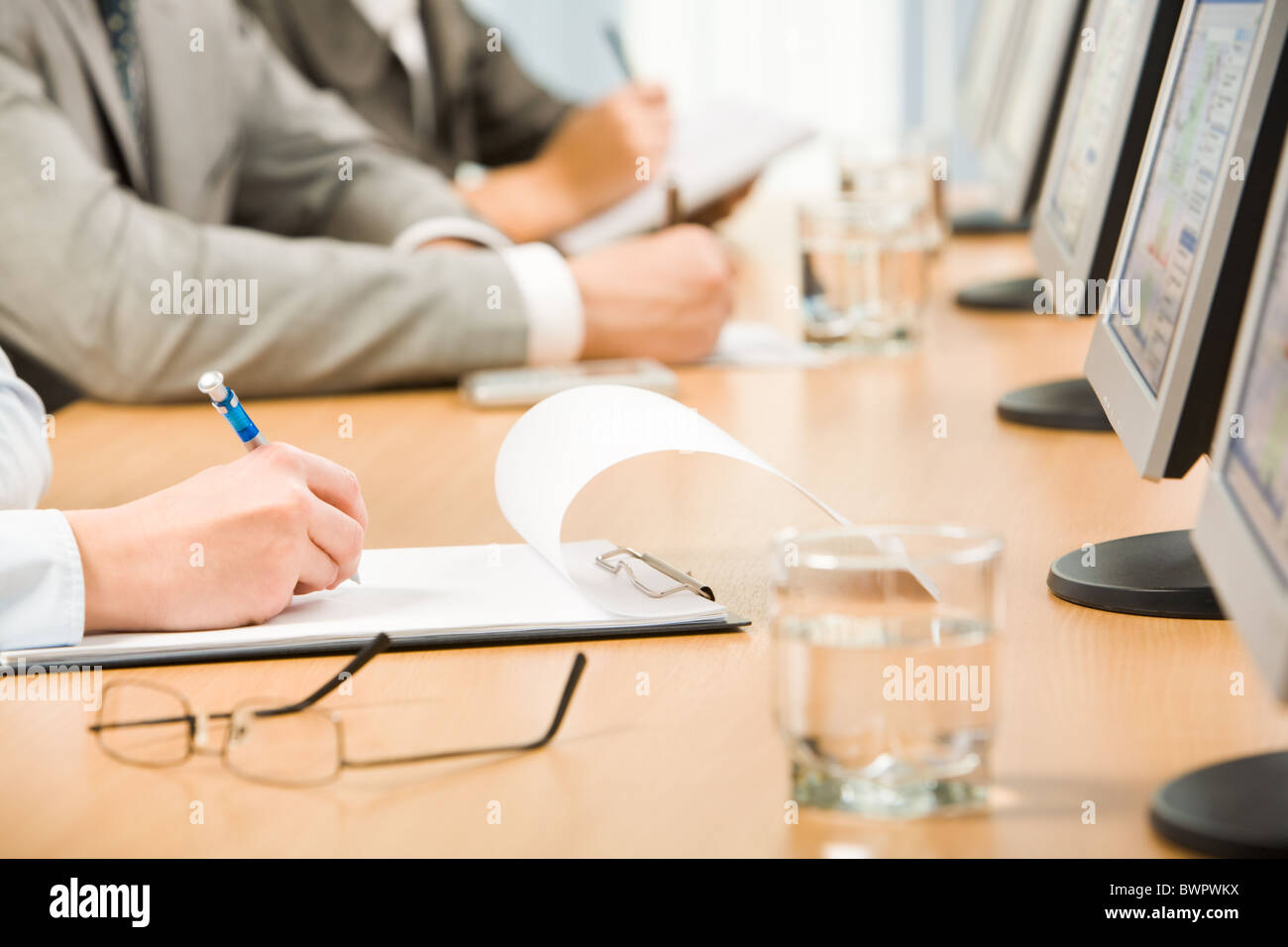 Image of human hand holding pen and making notes with glass of water, eyeglasses and monitors near by - Stock Image
