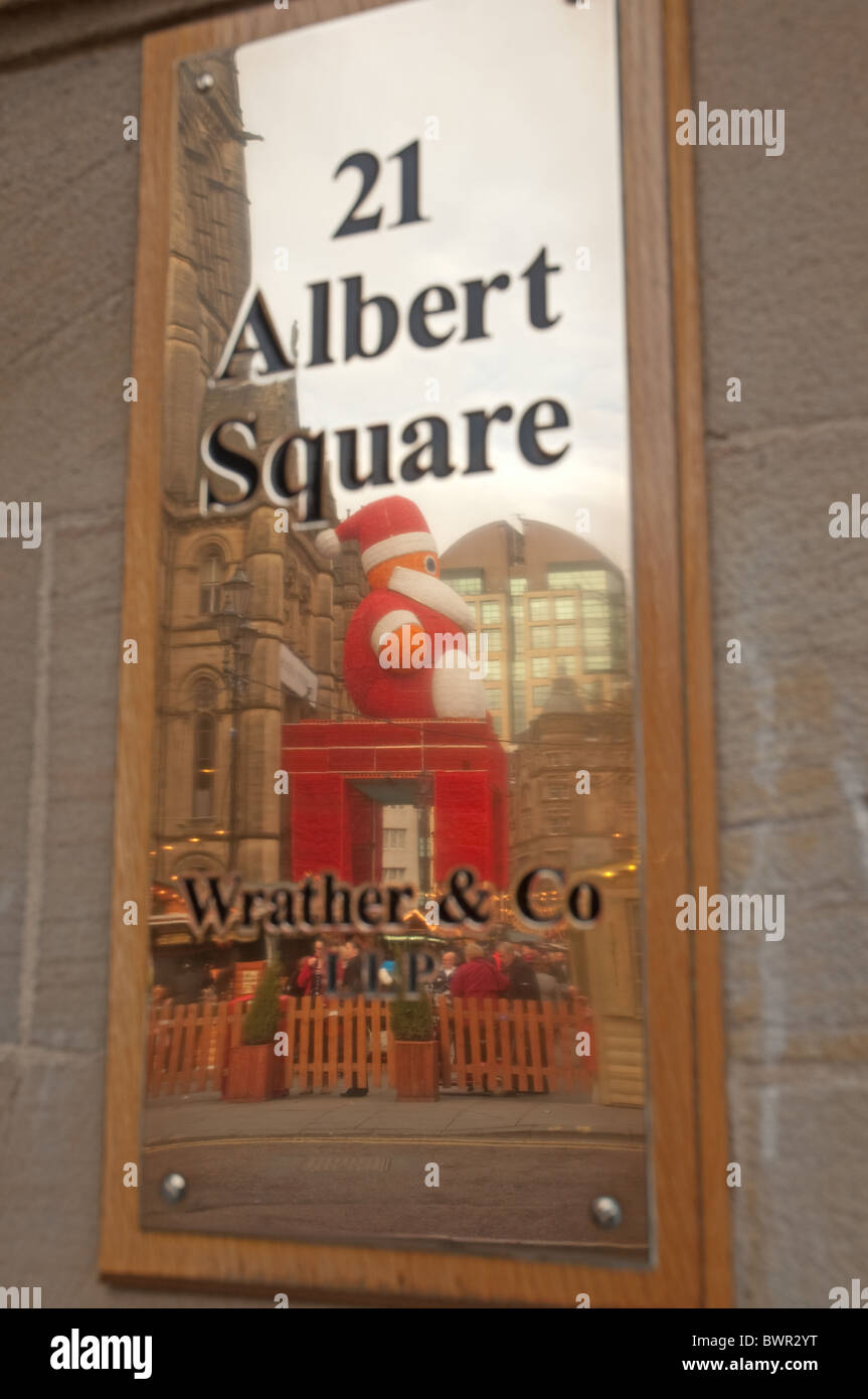 Father Christmas display out side Manchester Town Hall reflected in brass nameplate. - Stock Image