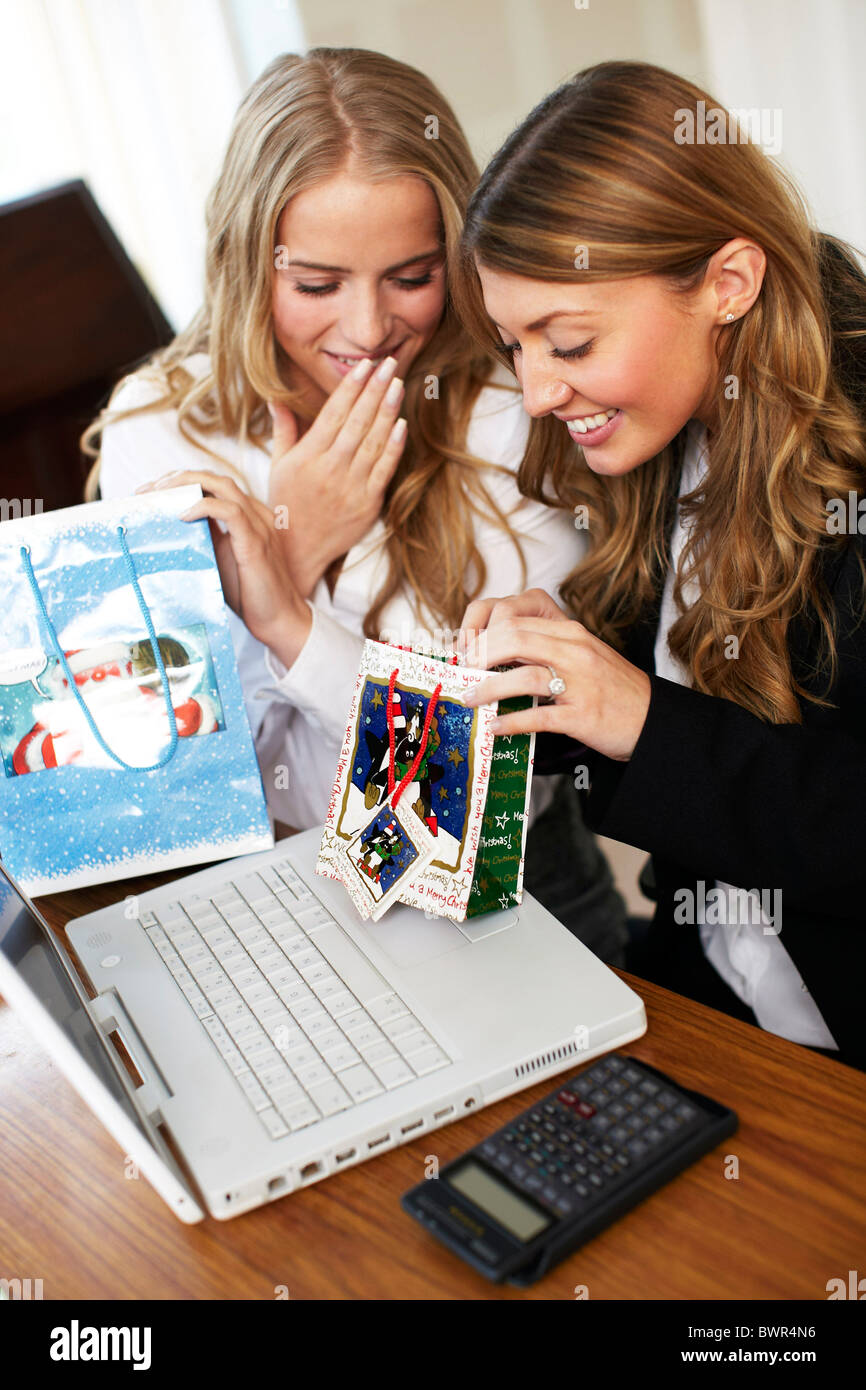 Girls in office opening secret Santa presents - Stock Image