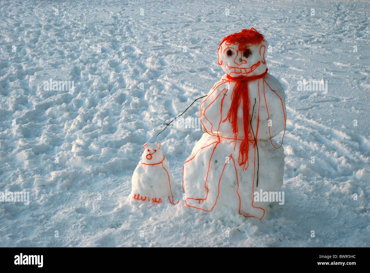 A 'cartoon' snowman with his dog, made from snow and wool, standing in the Meadows in Edinburgh, Scotland, - Stock Image