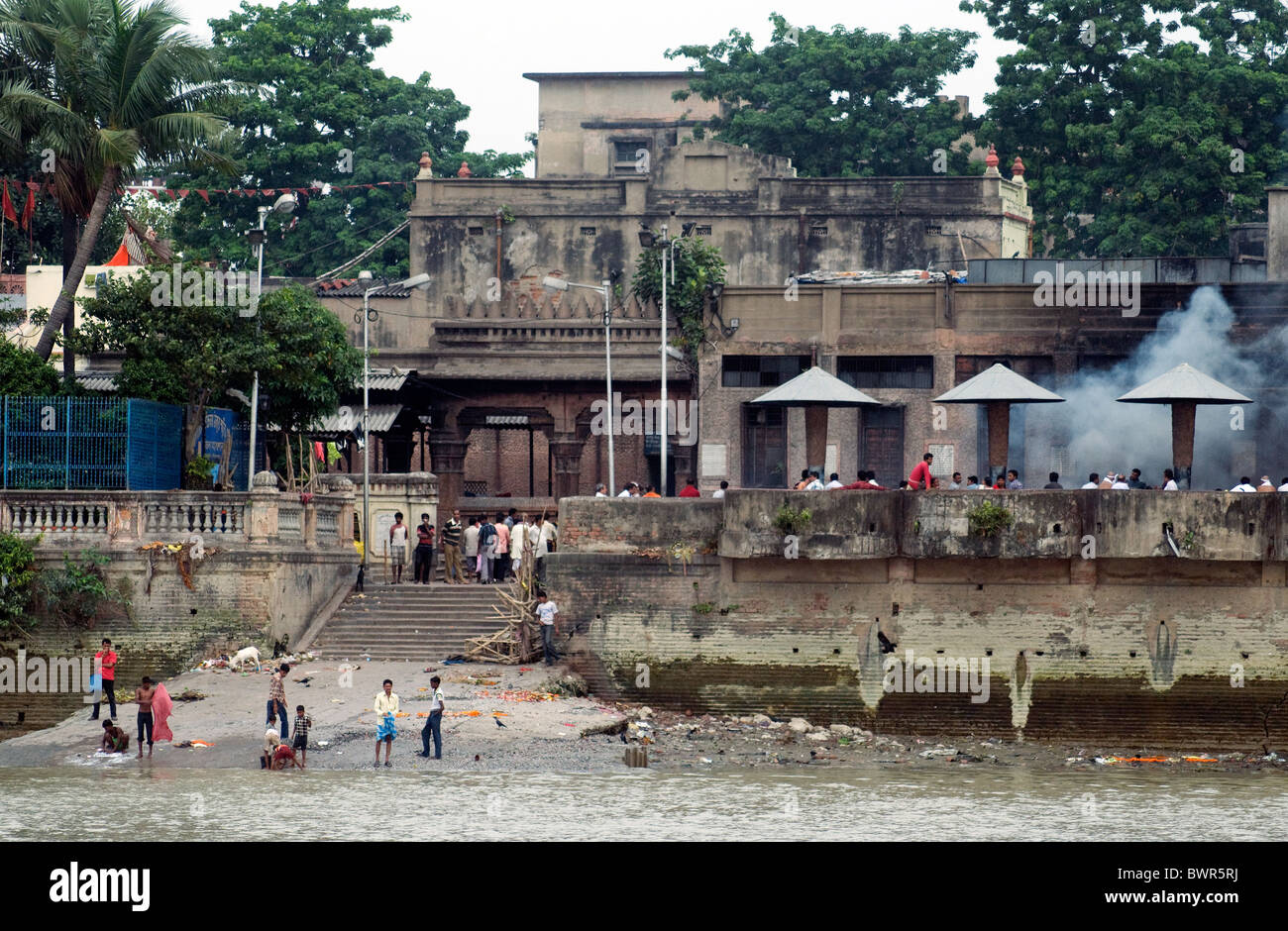 Rising smoke shows cremations are taking place at ghats on the Kolkata shore beside the Hooghly river - Stock Image