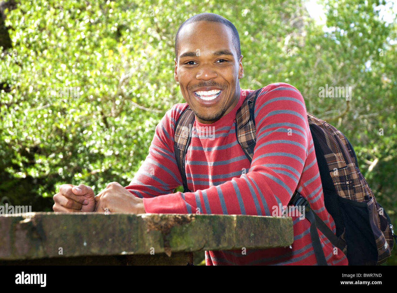 African American student wearing backpack sitting at outdoor table Stock Photo