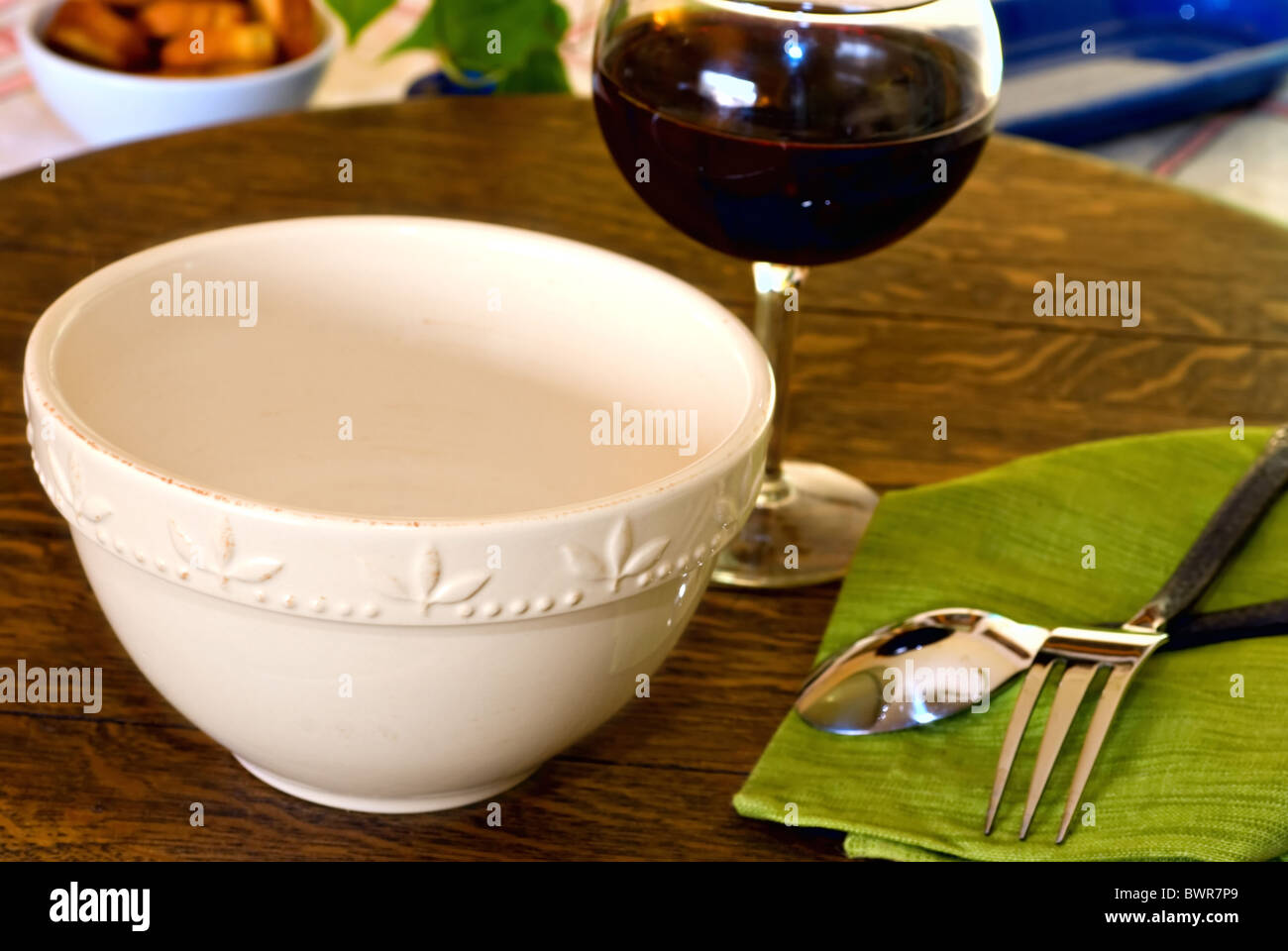 Empty white bowl on table with place setting and red wine Stock Photo