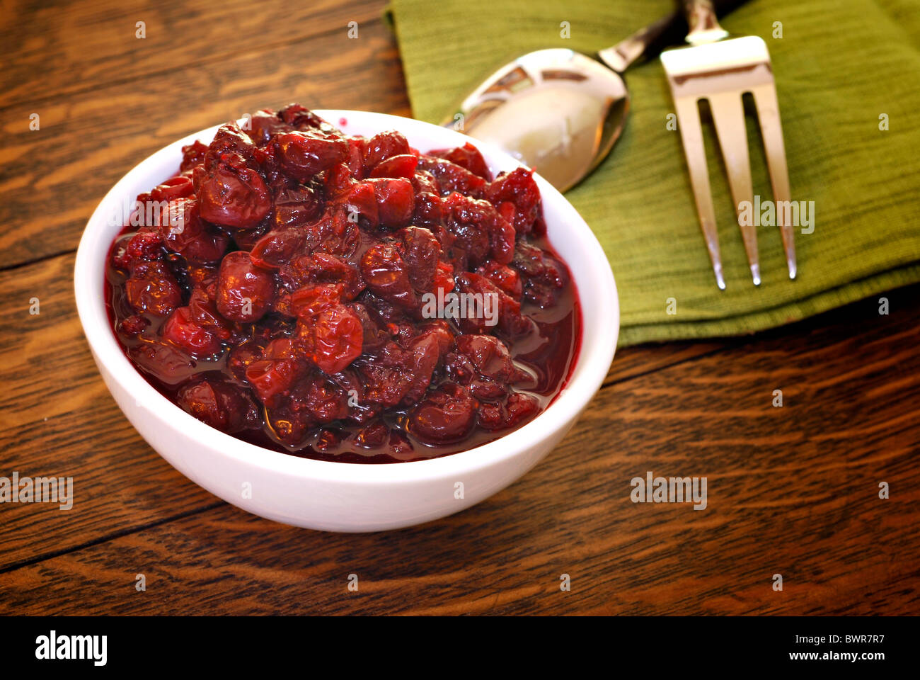 Bowl of fresh homemade cranberry sauce on antique oak table Stock Photo