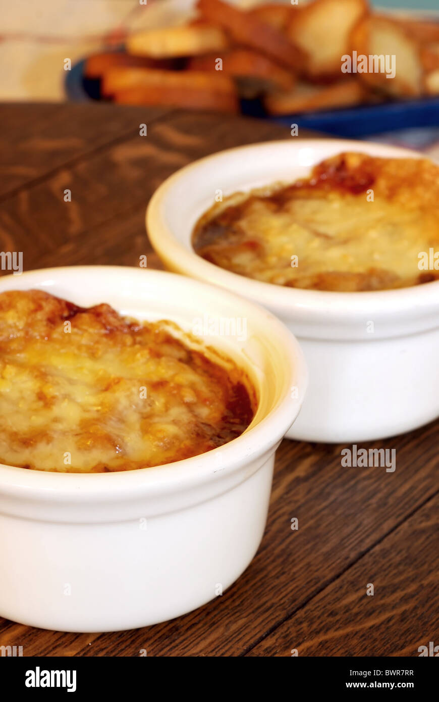Two bowls of French onion soup with mini toasts Stock Photo