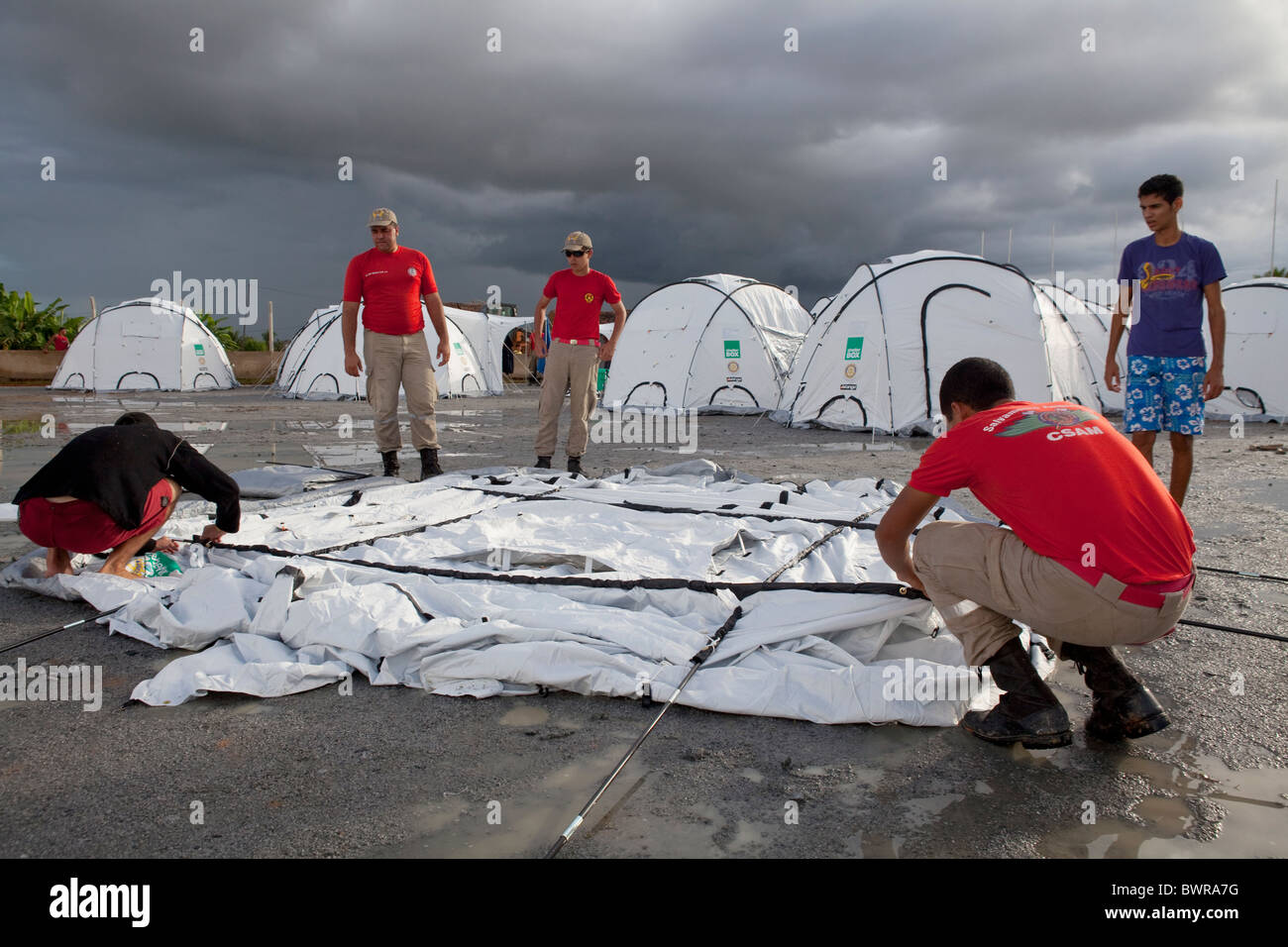 Members of Alegoas Fire Brigade assist in setting up tnets at Uniao Dos Palmares, Alegoas, Brasil - Stock Image
