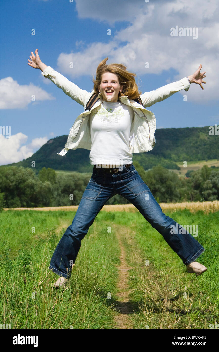 Woman caper lucky jump joy of life falling in love outside outdoors nature Jeans long hair jacket backpack - Stock Image