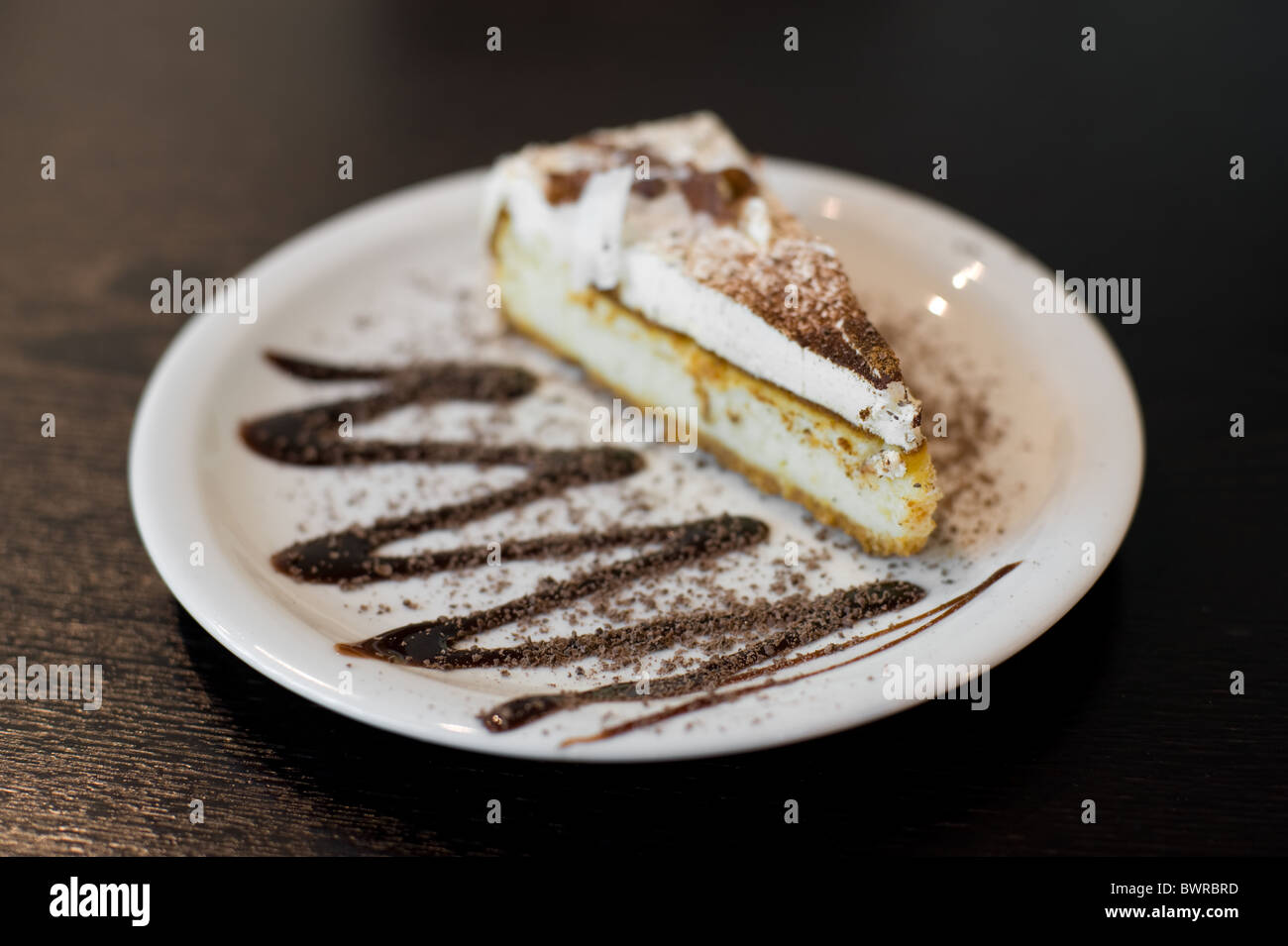 a piece of sponge cake with white cream and dusted with chocolate - Stock Image