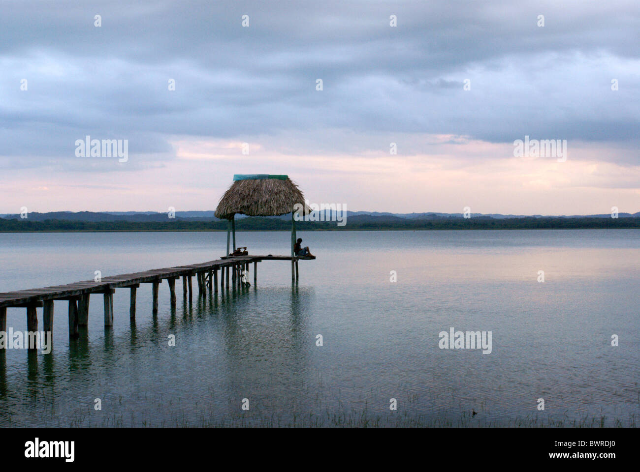 Person sitting on a wooden pier on Lake Peten Itza near Santa Elena, El Peten, Guatemala - Stock Image