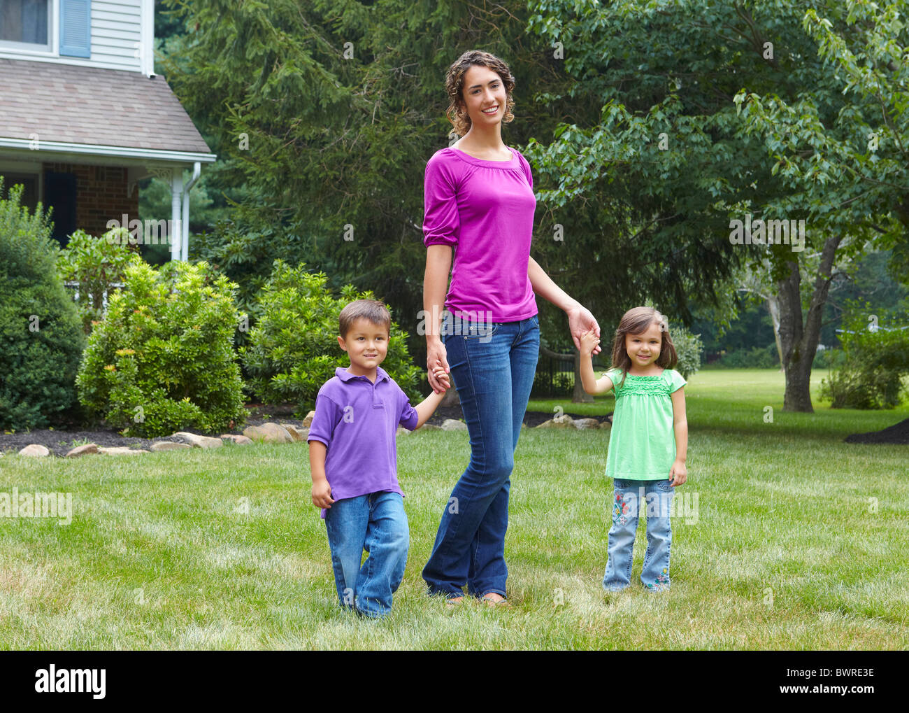 Mother holding hands with son and daughter in front yard Stock Photo