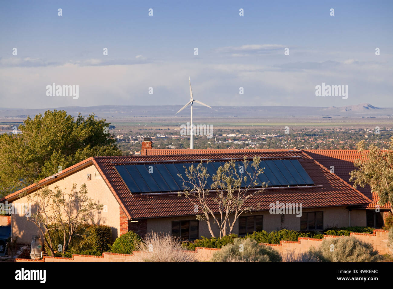 Solar panel on roof of home with wind turbine in background, Housing developments in Palmdale, Los Angeles County, - Stock Image