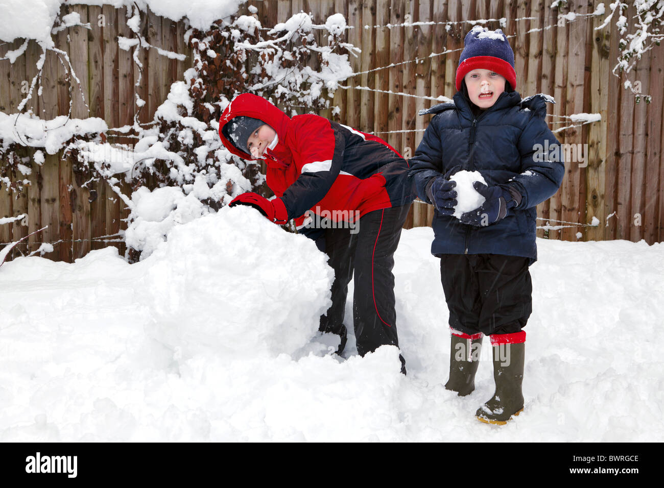 Two boys playing in the snow, one with a snowball and the other starting to build a snowman. - Stock Image