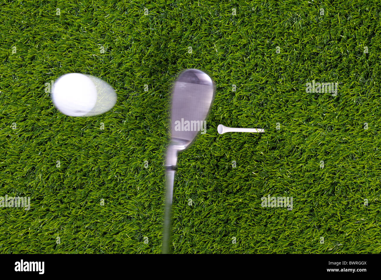 Photo of an iron hitting a golf ball off the tee with motion blur on the club and ball. Actual shot not photoshopped - Stock Image