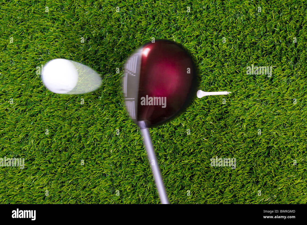 Photo of a driver hitting a golf ball off the tee with motion blur on the club and ball. Actual shot not photoshopped - Stock Image