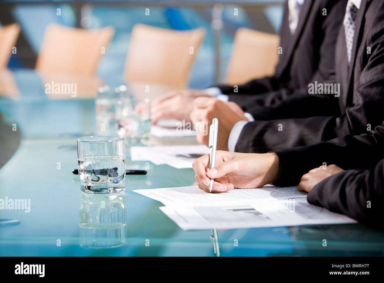 Row of human hands holding pen and making notes with glass of water near by - Stock Image