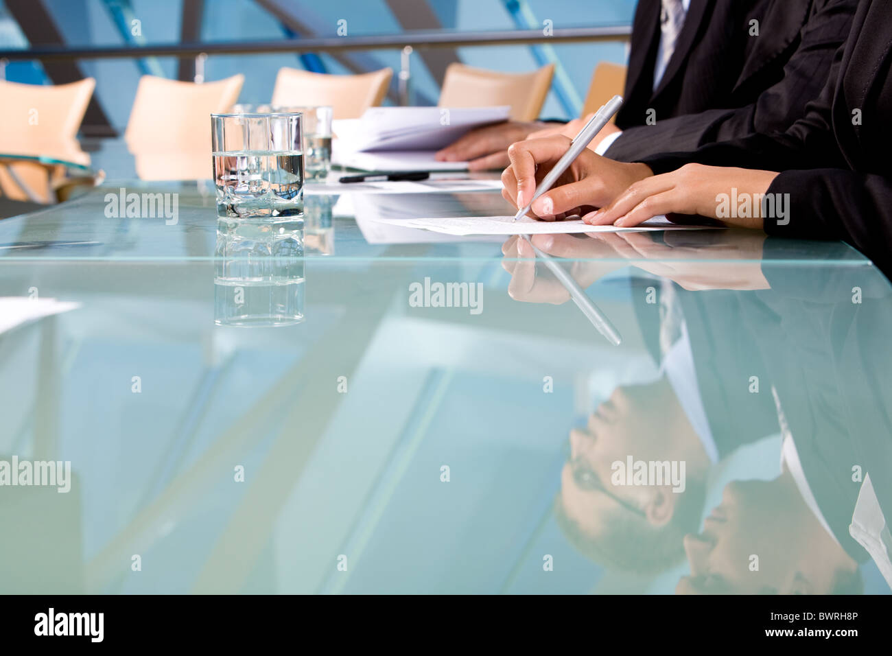 Human hands holding pen and making notes during conference - Stock Image