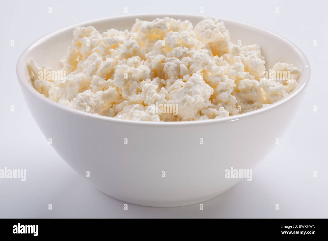 Bowl with fresh cottage cheese. Isolated on a white. - Stock Image