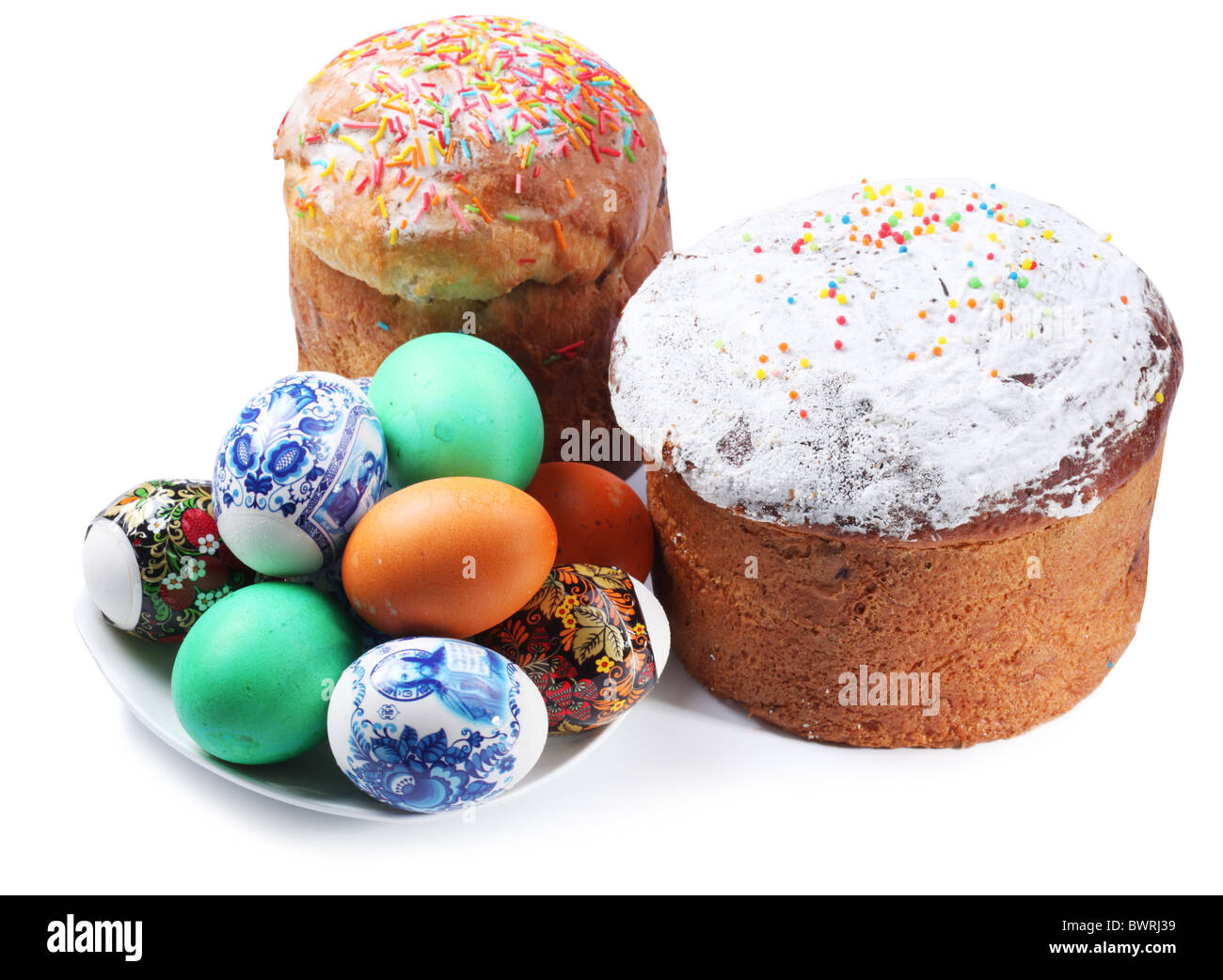 Multi-colored eggs on a plate and cakes. Easter holiday. Isolated on a white - Stock Image