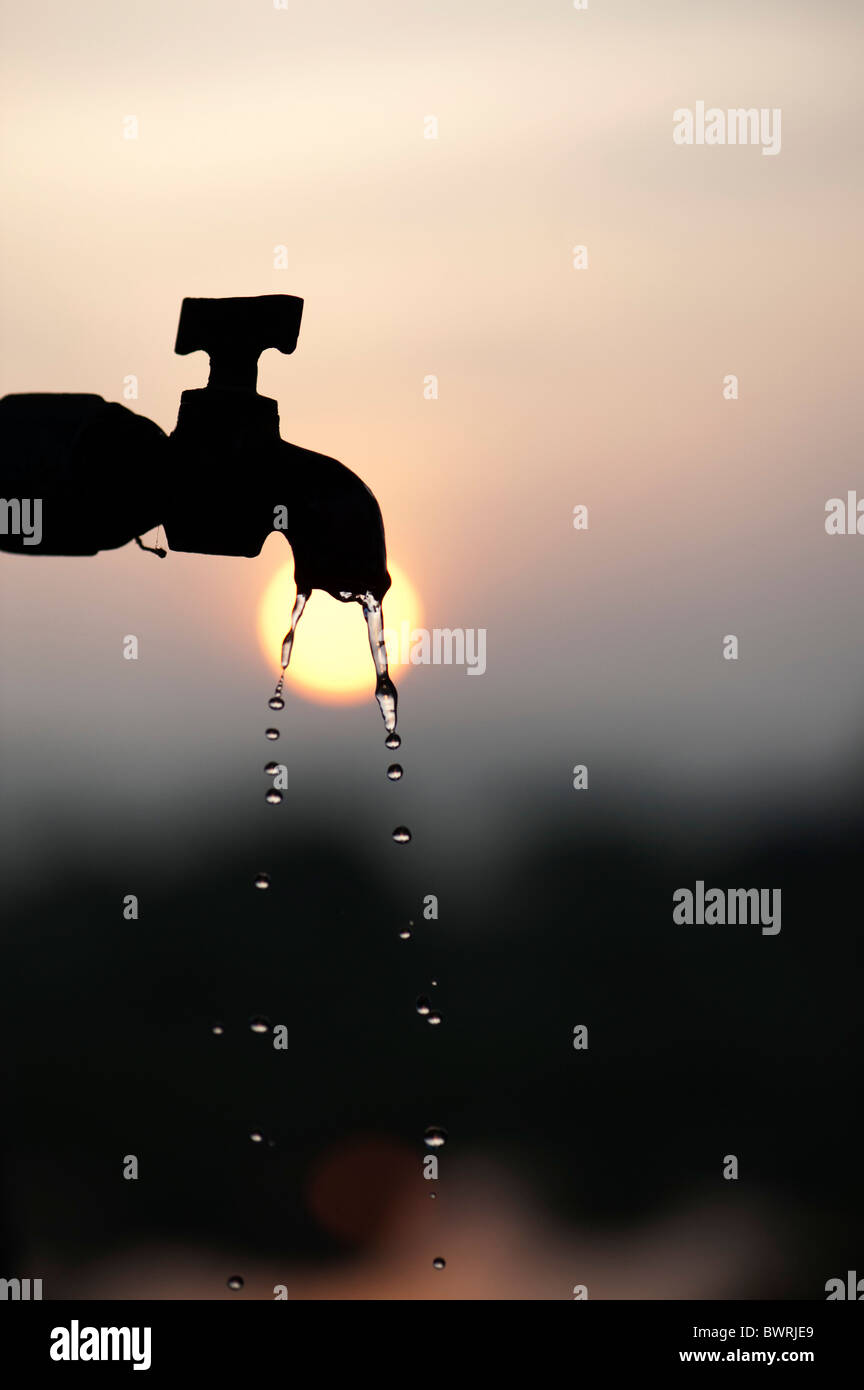 Silhouette of a stand pipe tap at sunrise with dripping water - Stock Image