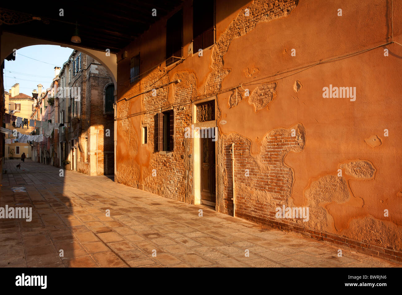 The afternoon sun lights up the Calle de le Colonne in the Castello district of Venice. - Stock Image
