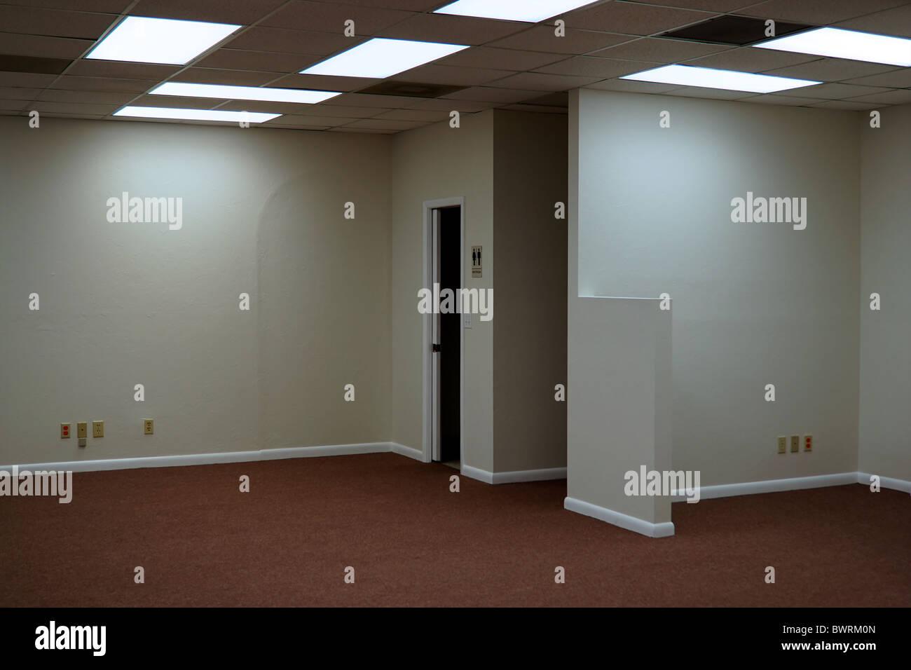 Inside empty office space lit by fluorescent ceiling light panels inside empty office space lit by fluorescent ceiling light panels showing open door to restroom aloadofball Gallery