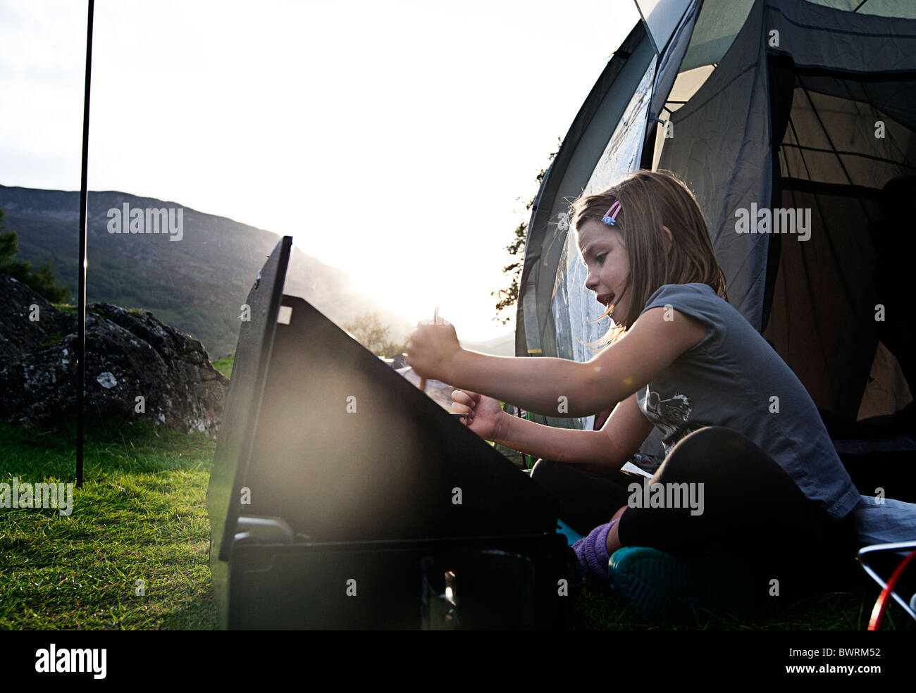 6 yr old girl cooking on stove whilst camping. Buttermere, Lake District - Stock Image