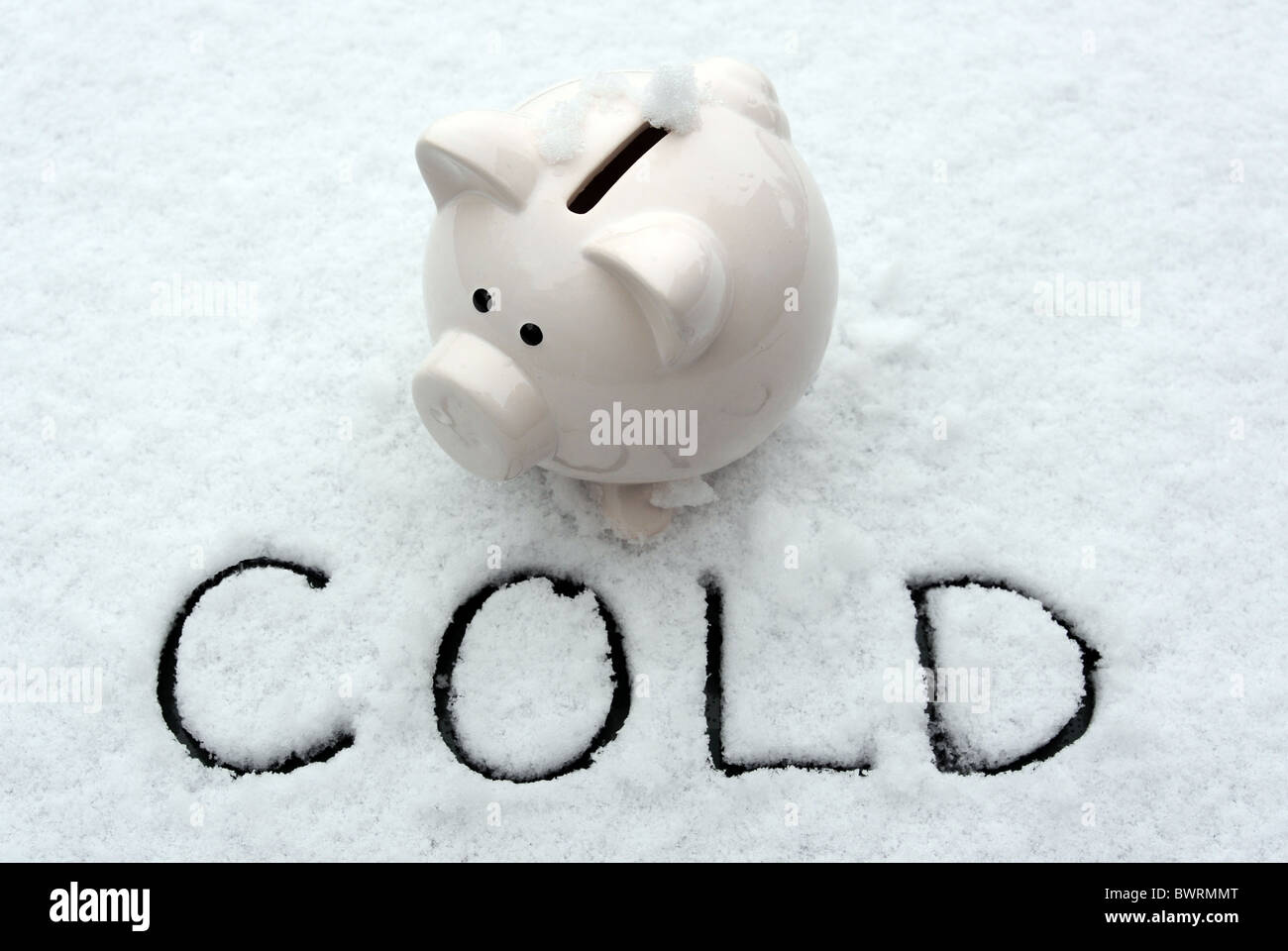 PIGGYBANK IN SNOW IN COLD FREEZING WINTER CONDITIONS RE FROZEN SAVINGS WINTER FUEL PAYMENTS INVESTMENTS ETC - Stock Image