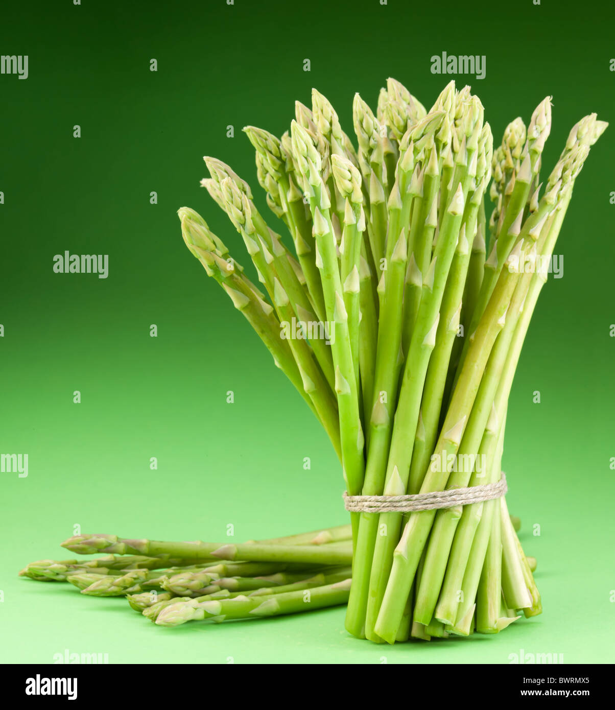 Sheaf of asparagus on a green background. - Stock Image