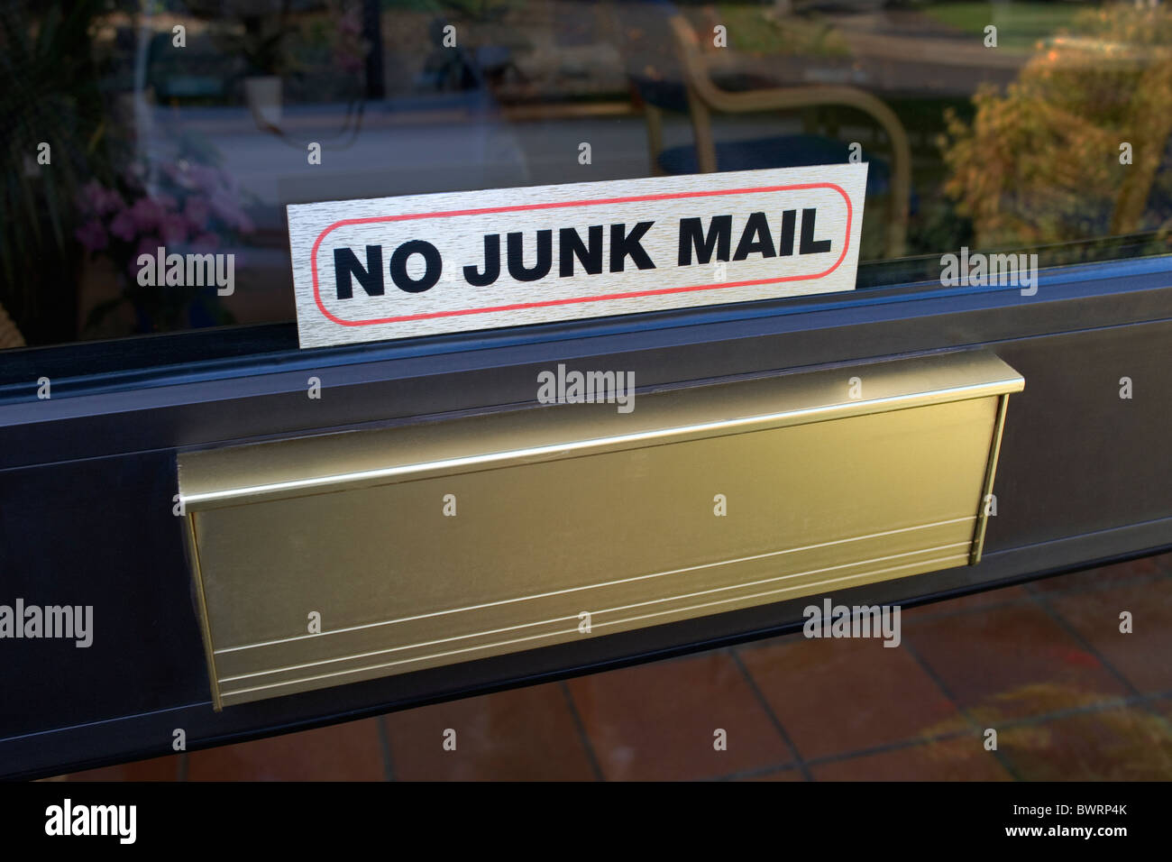A domestic letterbox with a notice saying : No junk mail - Stock Image
